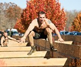Man Jumping on Tough Mudder Obstacle Course