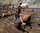 Woman Jumping on Tough Mudder Obstacle Course