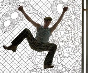 Man Climbing Lace Fence