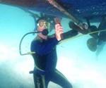Man Using Snorkel Hookah to Clean Boat Underside